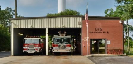 Station 15 on Hwy 27, bay doors open with 2 fire trucks inside, american flag on flag pole