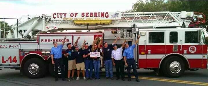 firemen who cooked in Chili Cook off taking photo in front of ladder truck 14