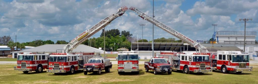 7 fire trucks lined up at fireman's field with both ladder trucks extended towards each other